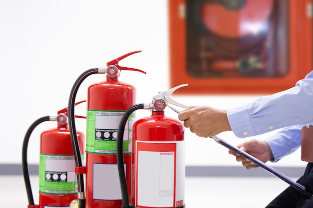 Ingénierie incendie vérifiant le niveau du manomètre du réservoir des extincteurs.