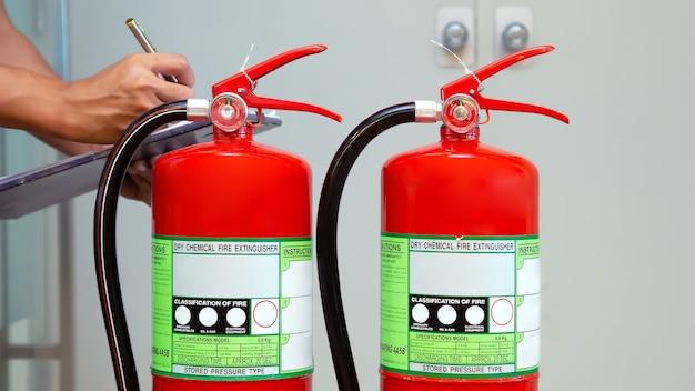 Ingénierie incendie vérifiant le niveau du manomètre de l'extincteur.