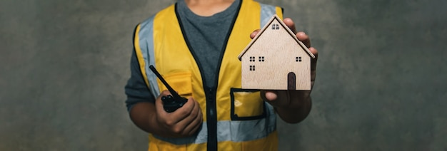 Ingénierie tenant une maison moderne en bois pour la réparation et la rénovation de biens immobiliers assurance habitation utilisation pour le site web avec bannière service client