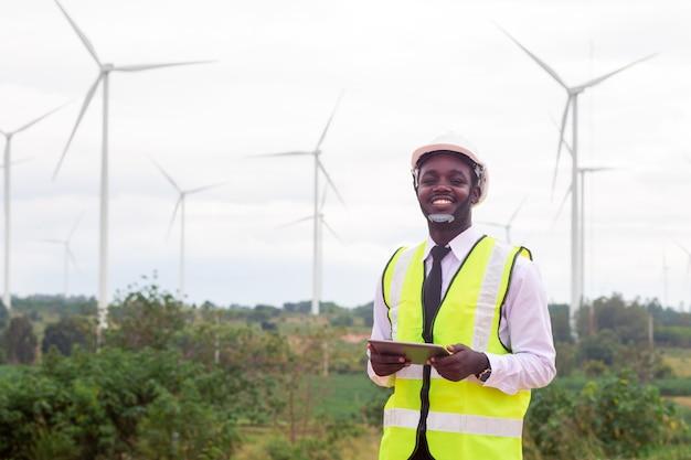 Ingénieur africain debout et ordinateur portable avec éolienne