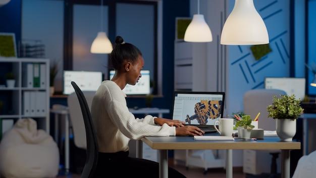 Ingénieur africain travaillant tard dans la nuit sur un modèle 3d d'engrenages industriels sur ordinateur portable faisant des heures supplémentaires dans le bureau de démarrage. indépendant étudiant une idée de prototype sur un ordinateur montrant un logiciel de cao sur l'écran de l'appareil