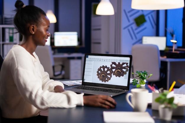 Ingénieur africain travaillant tard dans la nuit sur un modèle 3d d'engrenages industriels sur un ordinateur portable faisant des heures supplémentaires dans le bureau de démarrage