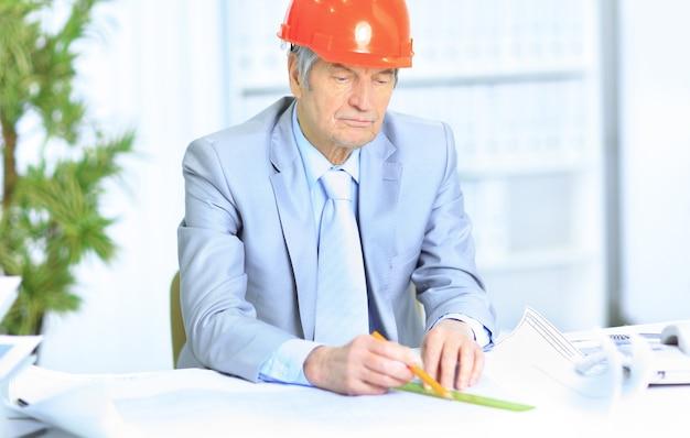 Ingénieur à l'âge de considérer les plans de dessin et de les corriger.