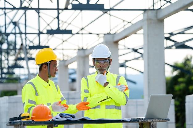 Ingénieur et architecte discutant d'une réunion avec un plan et des idées sur la structure du bâtiment sur le chantier de construction.