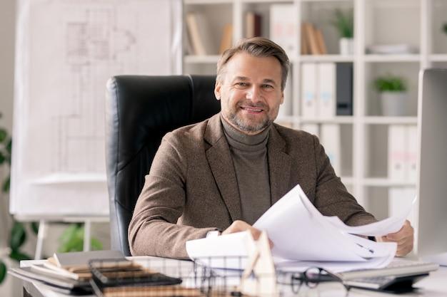 Ingénieur ou architecte mature réussi en tenue de soirée travaillant avec des papiers ou des plans tout en vous regardant par un bureau au bureau