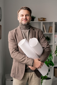Ingénieur ou architecte mature avec succès avec des plans laminés avec de nouveaux croquis debout devant la caméra au bureau