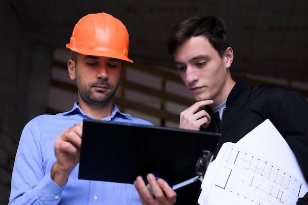 Ingénieur architecte portant un casque orange sur le site de travail expliquant les plans du projet au client