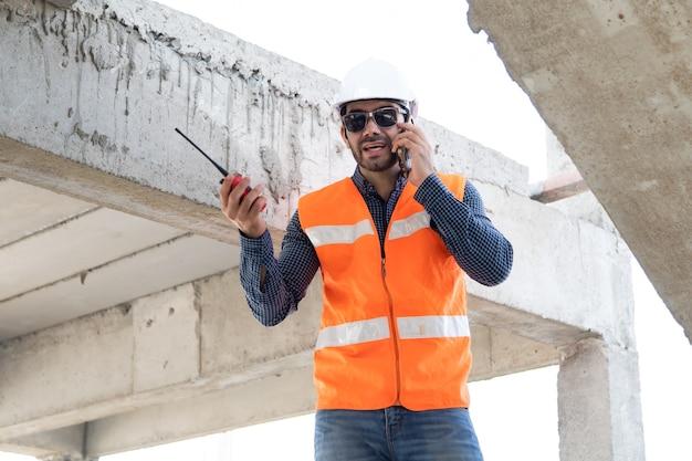 Ingénieur et architecte travaillant sur chantier avec impression bleue. électricien hispanique travaillant et à la recherche de plan dans un nouveau chantier de construction de maison.
