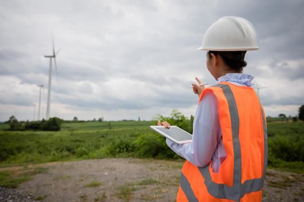 Ingénieur asiatique avec casque à l'aide d'un ordinateur tablette pc inspectant et travaillant à la ferme éolienne power generator station