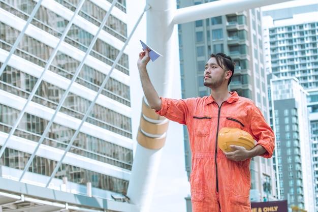 Ingénieur avec avion en papier. gai homme d'affaires tenant un avion