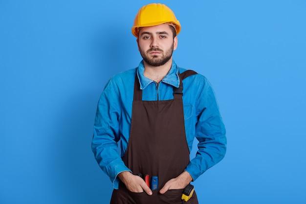L'ingénieur barbu attrayant européen portant un casque de protection jaune a l'air triste et fatigué, posant isolé sur un mur bleu, gardant les mains dans les poches.