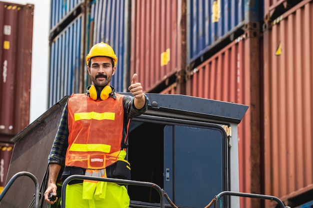 Ingénieur barbu debout avec un casque jaune pour contrôler le chargement et vérifier la qualité des conteneurs du navire de fret pour l'importation et l'exportation au chantier naval ou au port