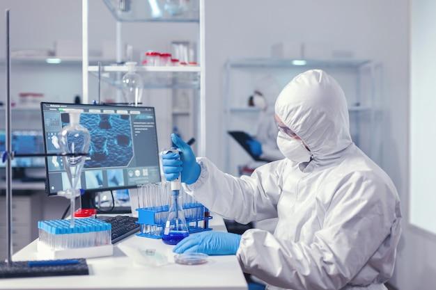 Ingénieur en biochimie réalisant une expérience sur le coronavirus à l'aide d'une pipette automatique. chimiste dans un laboratoire moderne faisant des recherches à l'aide d'un distributeur pendant l'épidémie mondiale de covid-19.
