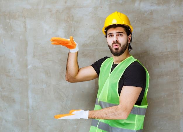 Ingénieur en casque jaune et gants industriels montrant la hauteur d'un objet