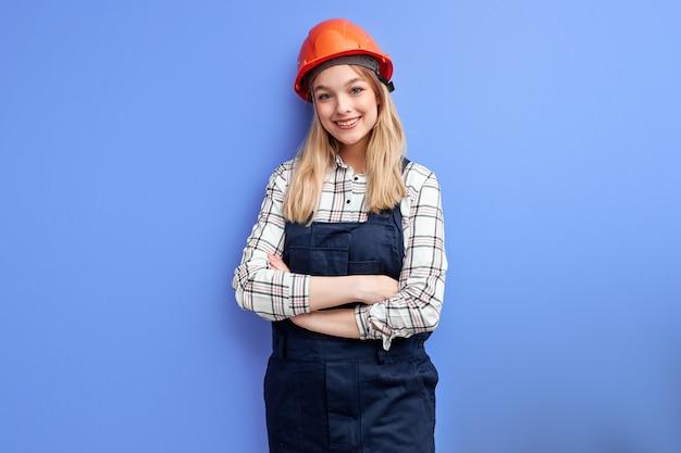 Ingénieur avec casque orange debout avec une expression positive, vêtu d'un uniforme de salopette de constructeur et regardant la caméra sur fond bleu