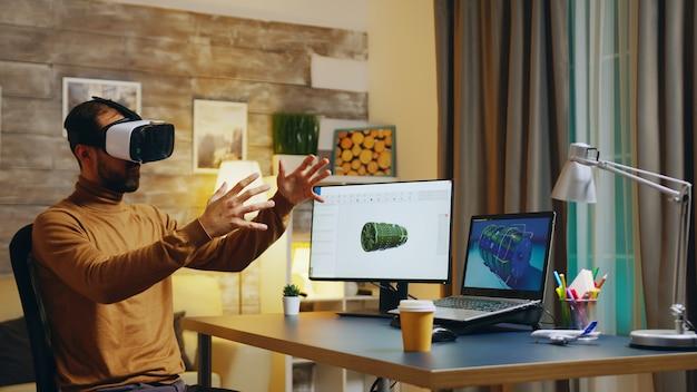 Ingénieur avec casque de réalité virtuelle à son bureau pendant la nuit travaillant sur une nouvelle technologie pour les turbines.