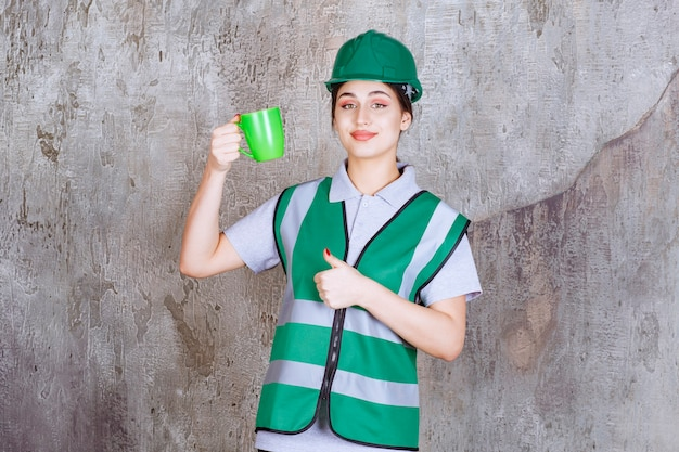Ingénieur en casque vert tenant une tasse de café vert et montrant un signe de plaisir.