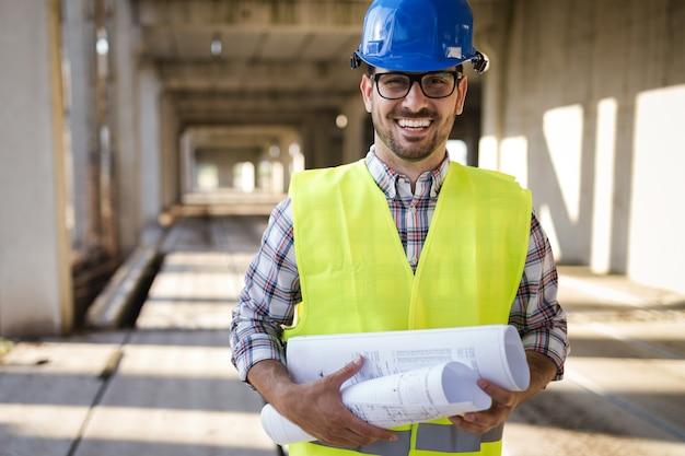 Ingénieur de chantier de construction de jeune homme d'affaires avec impression bleue