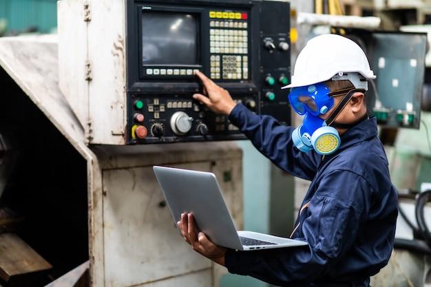 Ingénieur en chef asiatique dans le casque et travaillant sur ordinateur portable sur la pièce mécanique à l'ancien équipement d'usine.