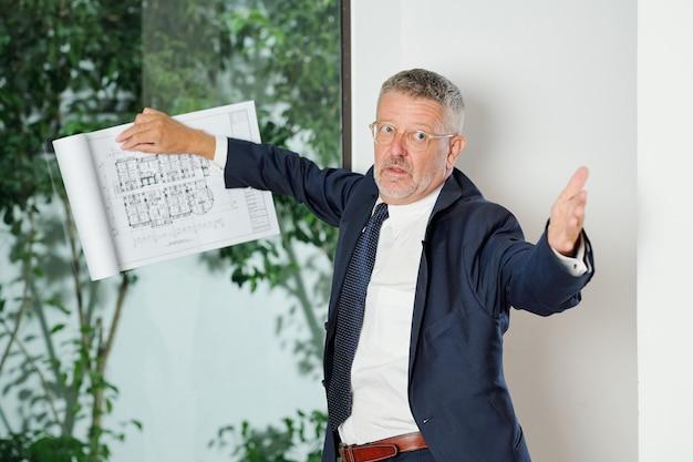 Ingénieur en chef sérieux senior avec plan de construction demandant à des collègues de faire des corrections dans la mise en page