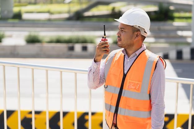 Ingénieur civil asiatique fonctionne avec la radio pour contrôler le travail à la construction