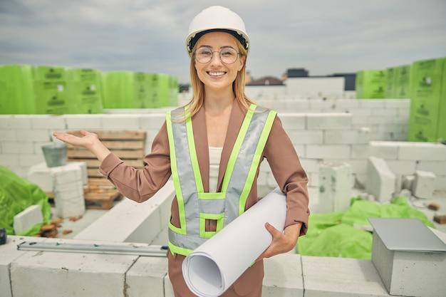 Ingénieur civil blond souriant dans un casque de sécurité invitant les clients à un nouvel objet de construction