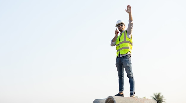 L'ingénieur civil du moyen-orient exploite le travailleur à la radio pour contrôler le travail sur le chantier de construction.