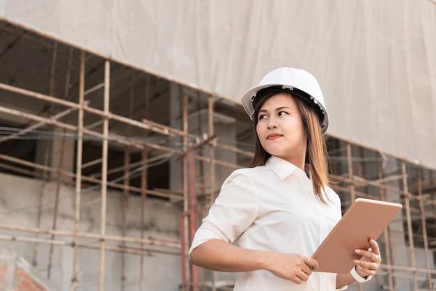 Ingénieur civil de femme asiatique avec un chantier de construction de casque de sécurité blanc.