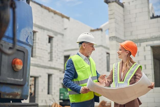 Ingénieur civil senior joyeux et une femme blonde souriante surveillante de la construction se regardant