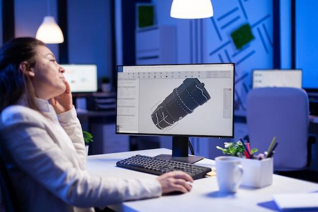 Ingénieur concepteur de projet analysant l'idée conceptuelle du modèle 3d de l'usine qui bâille en faisant des heures supplémentaires
