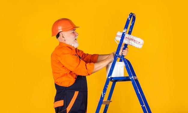 Ingénieur constructeur architecte. l'homme utilise un rouleau sur une échelle. travail en appartement. artisan avec rouleau à peinture. entreprise de peinture et rénovation de maison. faire l'outil de réparation. peintre travaillant au chantier de construction.