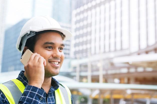 Ingénieur constructeur arpenteur avec l'équipement de transit de théodolite au chantier de construction