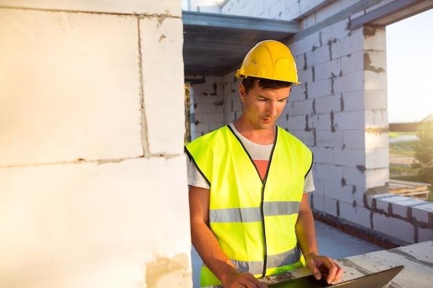 Ingénieur de construction sur le chantier de construction d'une maison faite de blocs de béton poreux