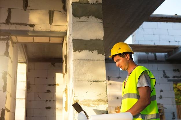 Ingénieur en construction sur le chantier de construction d'une maison travaille sur un ordinateur, projet de dessins