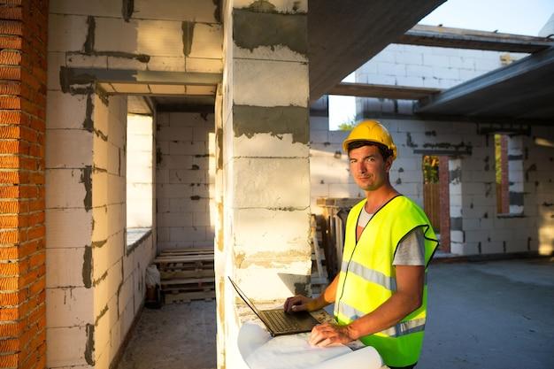 Ingénieur en construction sur le chantier de construction d'une maison travaille à un ordinateur