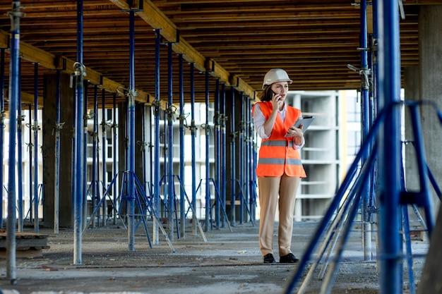 Ingénieur de construction féminin. architecte avec une tablette sur un chantier de construction. jeune femme à la recherche, lieu de chantier sur fond. notion de construction.