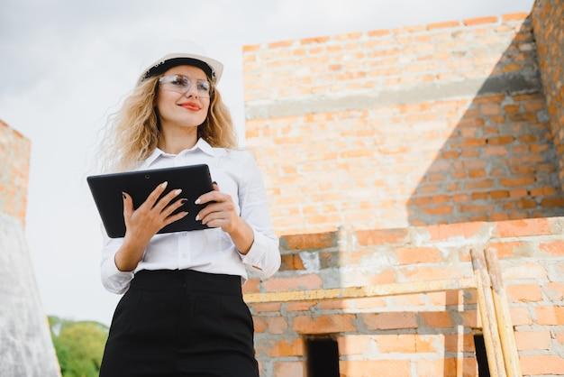 Ingénieur de construction féminin. architecte avec une tablette sur un chantier de construction. jeune femme à la recherche, lieu de chantier sur fond. notion de construction