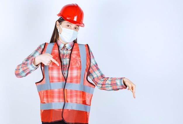 Ingénieur en construction féminin en casque rouge et masque de sécurité pointant vers le bas