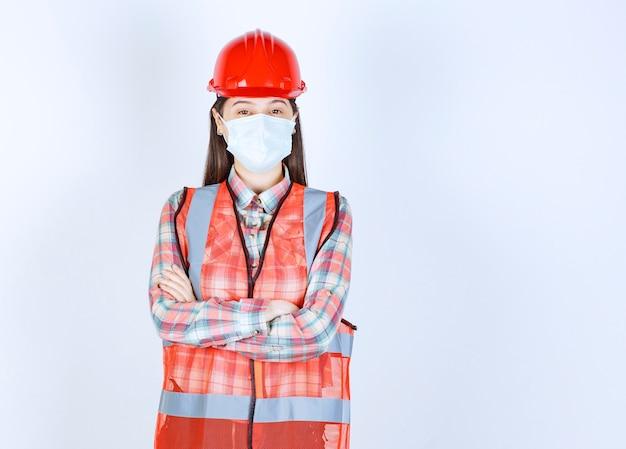 Ingénieur en construction féminin en casque rouge et masque de sécurité