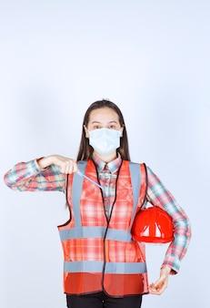 Ingénieur en construction féminin dans un masque de sécurité et un casque rouge sous ses bras tenant un stylo