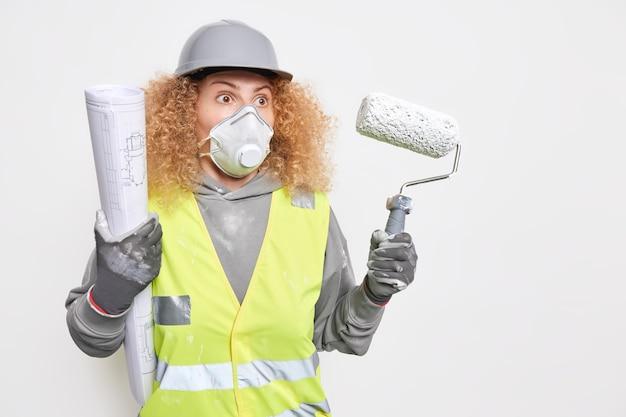 L'ingénieur de construction féminin tient le projet architectural et le rouleau de peinture