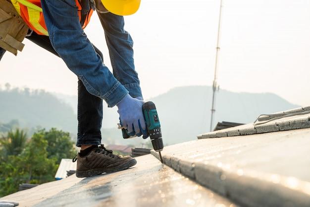 Un ingénieur en construction porte un uniforme de sécurité installe le nouveau toit, le couvreur utilise un pistolet à clou pneumatique ou pneumatique et installe une tuile en béton sur le toit supérieur.
