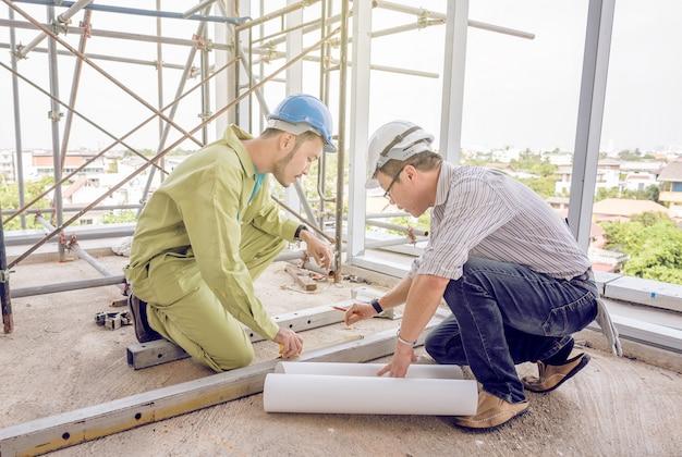 Ingénieur en construction principal contrôlant le travailleur au chantier de construction.