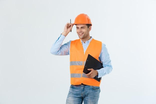 Ingénieur en construction souriant posant isolé sur fond gris.