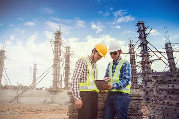 Ingénieur et contremaître utilisant une tablette pour travailler sur un chantier