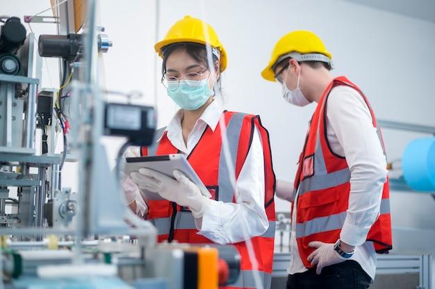 Ingénieur de contrôle qualité (qc) surveillant et vérifiant le système de machine dans l'usine de fabrication