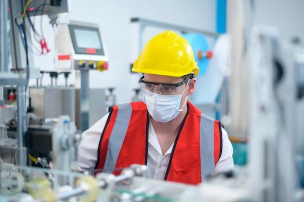 Ingénieur de contrôle de la qualité (qc) surveillant et vérifiant le système de machine dans l'usine de fabrication