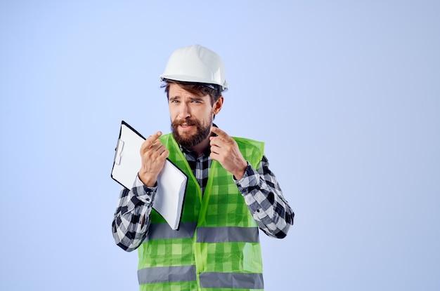 Ingénieur dans un fond bleu de conception de travaux de vestconstruction vert. photo de haute qualité