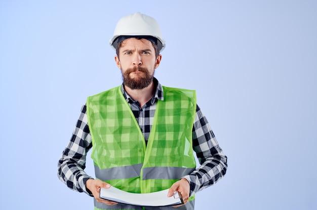 Ingénieur dans un fond bleu de conception de travaux de vestconstruction vert