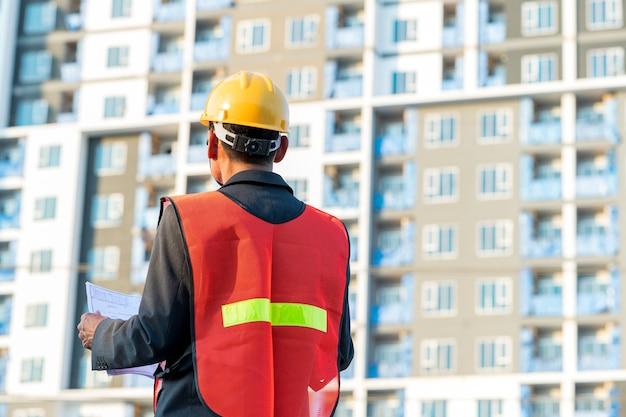 Ingénieur debout pour inspecter les plans de construction sur le chantier de construction